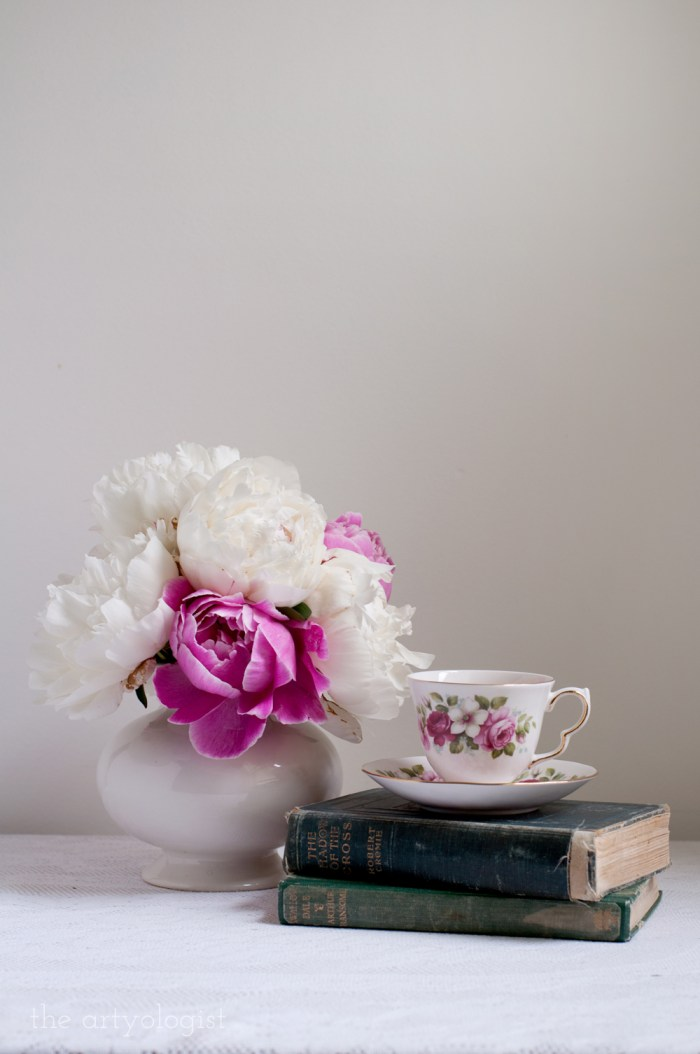 a bouquet, stack of books and a teacup atop a table