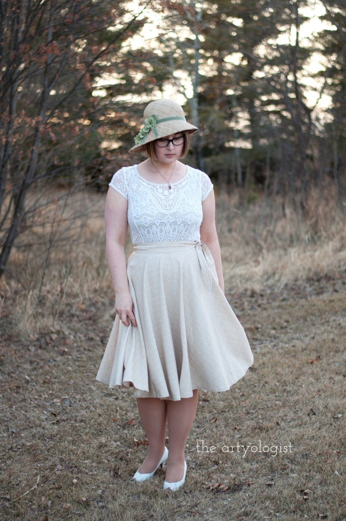 nicole wearing a tan wrap skirt, lace blouse and straw cloche with green flowers on it
