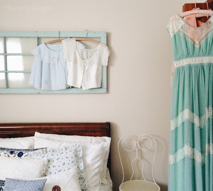 pretty vintage dresses and bedjackets hanging on an old window frame over a bed