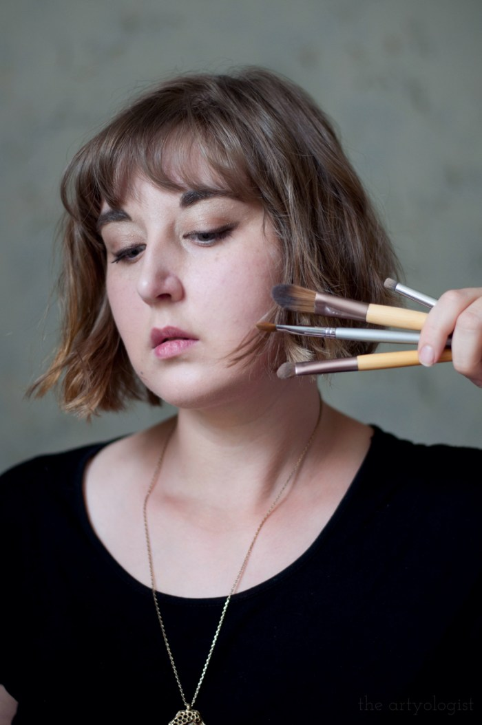 woman holding makeup brushes up to her face showing an everyday makeup look