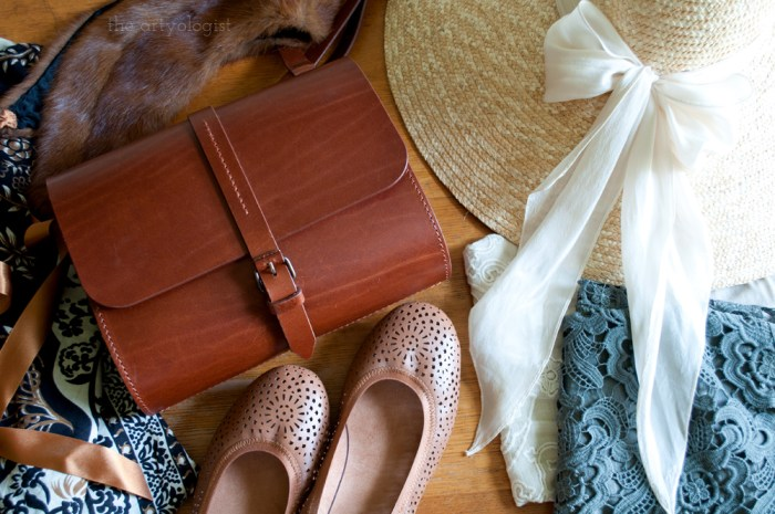 flat lay of a purse, straw hat, shoes and clothes