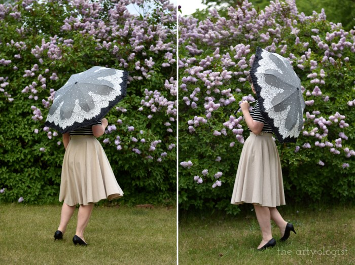 woman twirling in front of a hedge holding a lace parasol