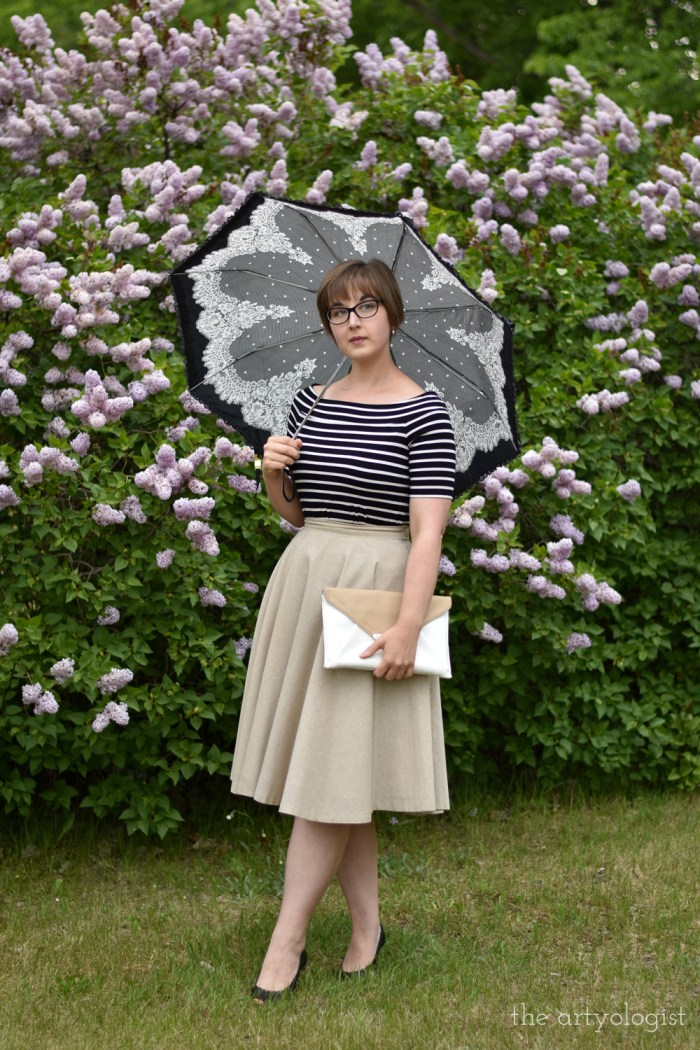 woman wearing a striped off the shoulder t-shirt, tan skirt, parasol and high heels in front of a lilac hedge