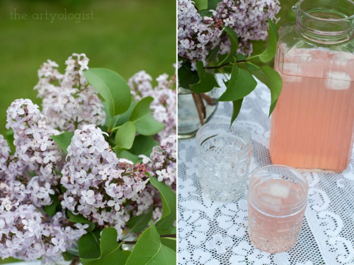 a pitcher of pink raspberry lemonade on a table beside a bouquet of lilacs
