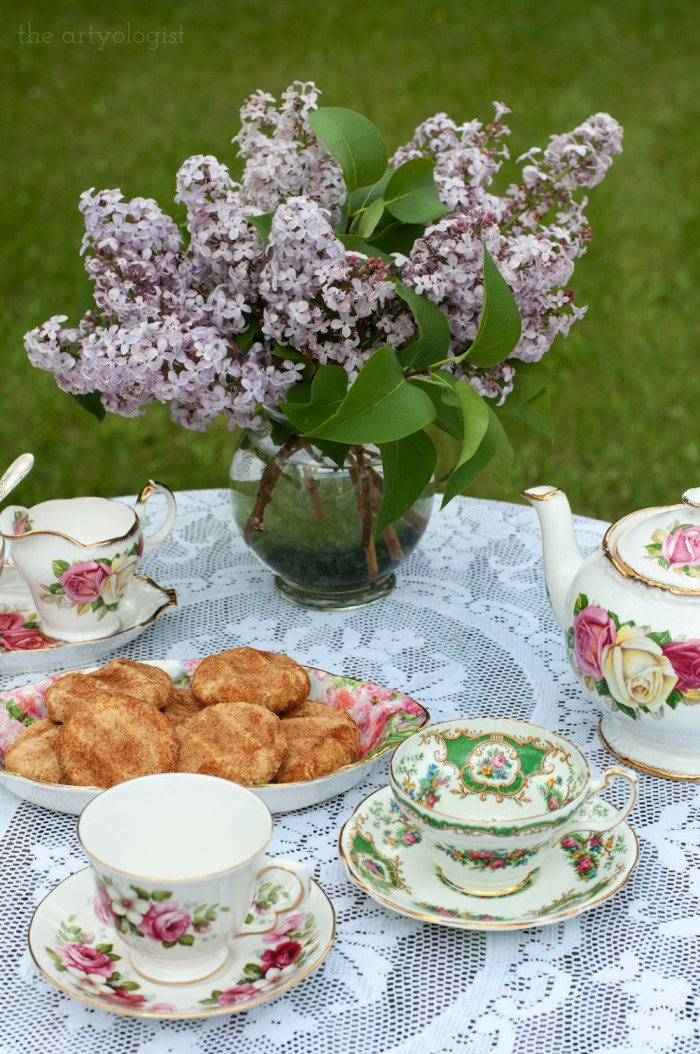 a bouquet of lilacs and teacups on a table with a white tablecloth