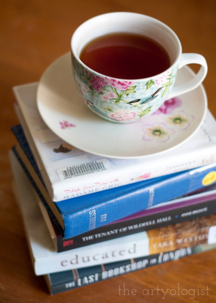 stack of books with a cup of tea on top