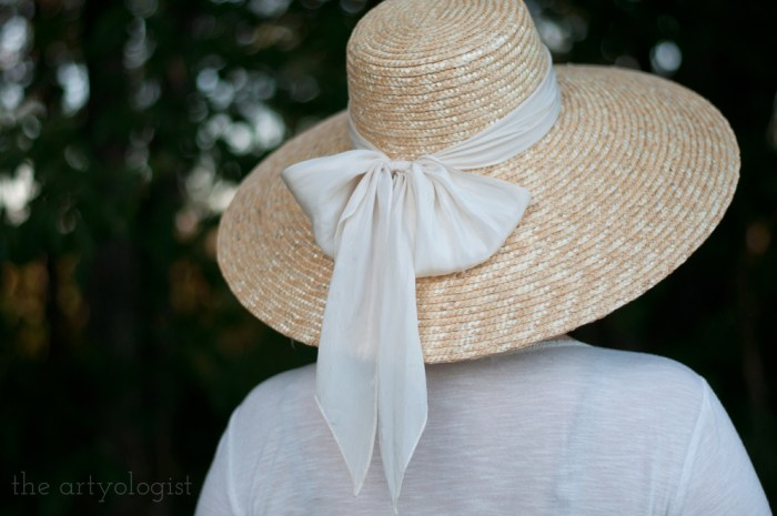 woman wearing a straw hat with a scarf bow
