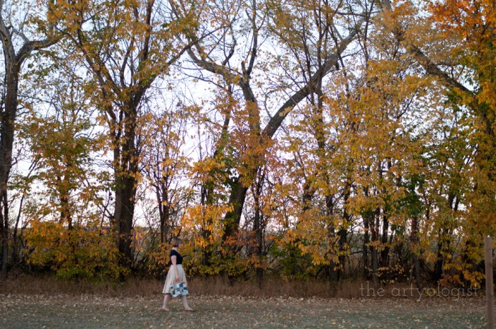 woman walking in front of a large row of trees