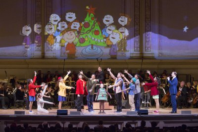 """Members of the TADA! Youth Theater with narrator John Bolton and music director Steven Reineke with the New York Pops and Essential Voices USA in the Carnegie Hall Family Concert """"A Charlie Brown Christmas"""" (Photo credit: Richard Termine)"""