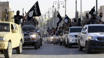 Militant Islamist fighters parade on military vehicles along the streets of northern Raqqa province