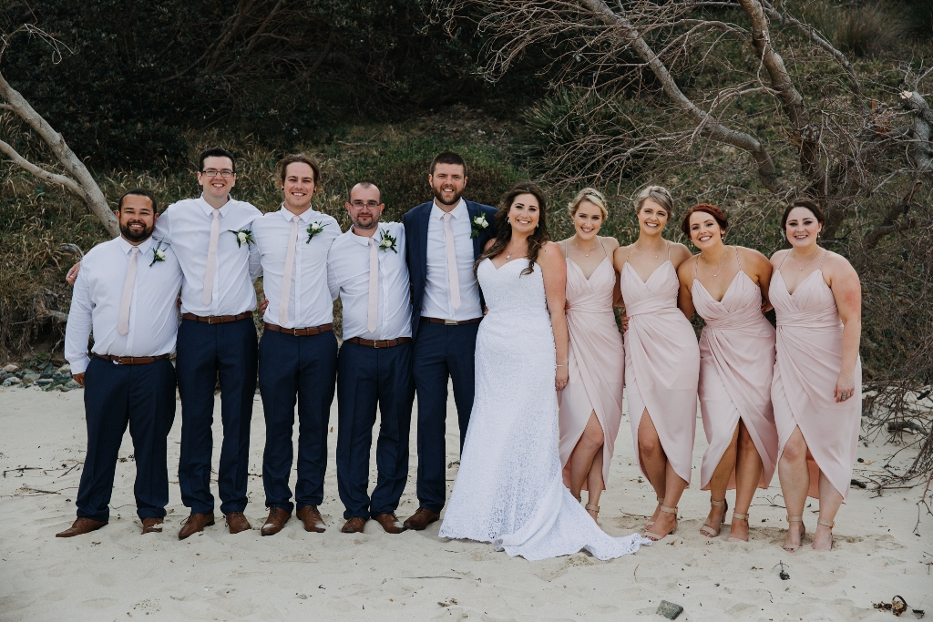Bridal party standing on beach