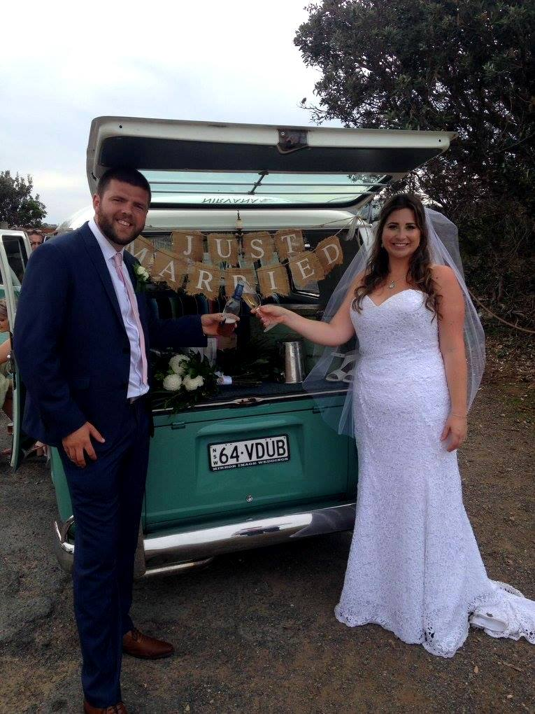 Bride and Groom cheersing in front of Just Married car sign
