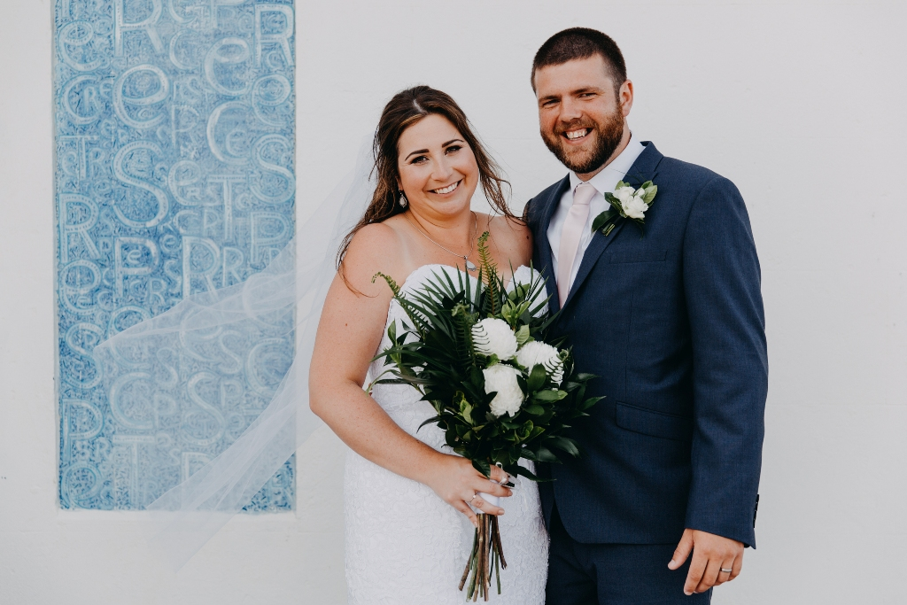Bride and Groom smiling in front of white and blue wall