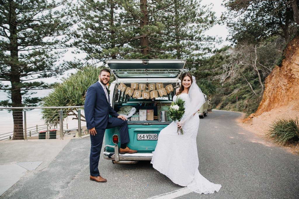Bride and Groom standing in front of Just Married VW Kombi