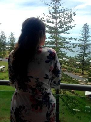 Bride looking over balcony in robe