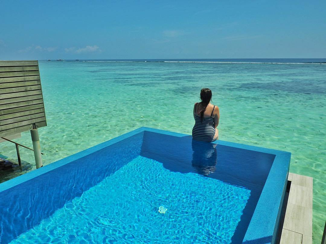 Girl sitting on Infinity Pool in Maldives