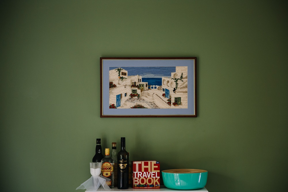 Greek Islands artwork above wine rack