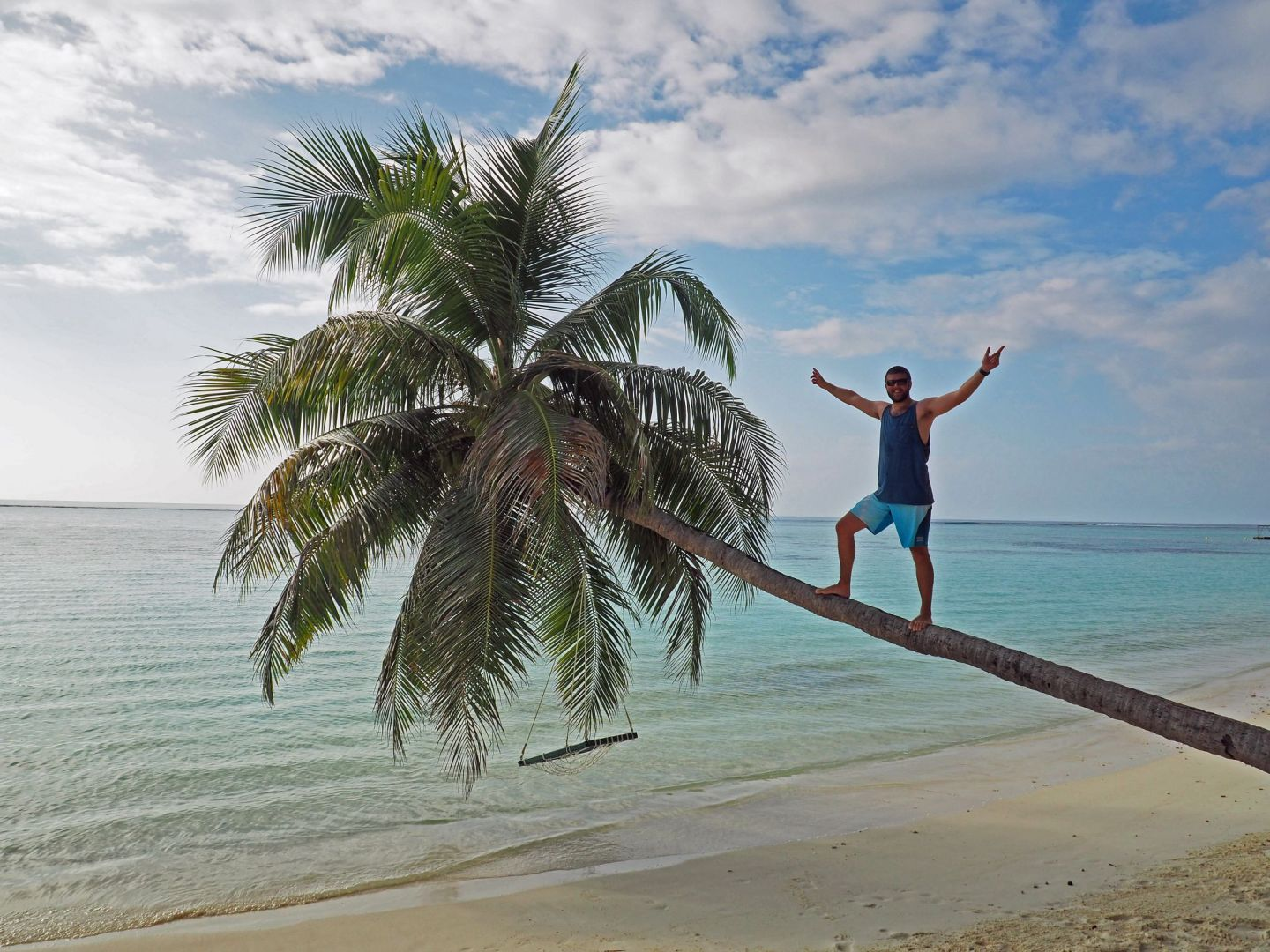 Dan on palm tree over water in Maldives