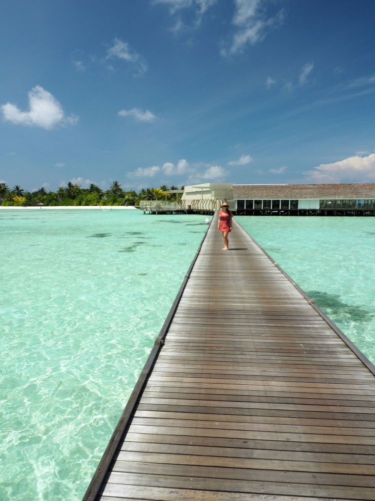 Girl on walkway over water LUX Maldives