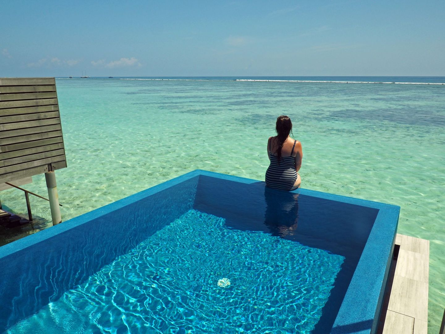 Girl sitting on edge private Infinity Pool LUX Maldives