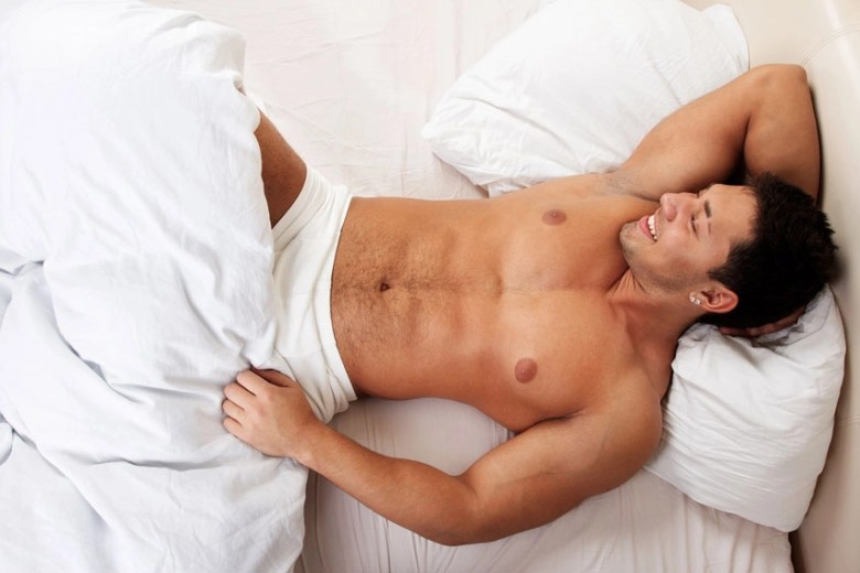 beautiful man laying on bed