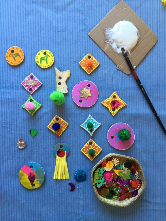 kids decorate recycled cardboard shapes with pompoms and sequins to make sustainable junk unicorn necklaces free printable