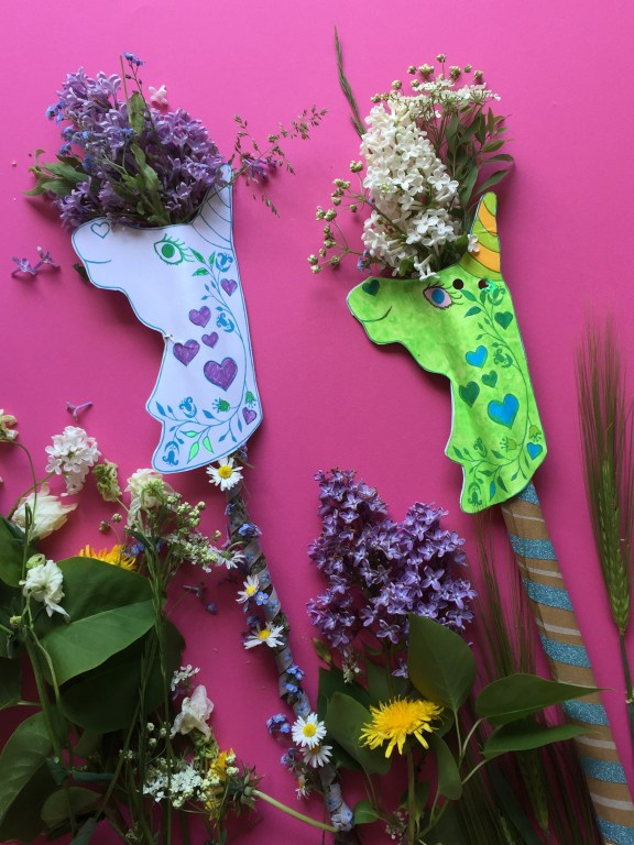 two cardboard unicorn wands decorated with lilacs and garden foliage made with recycled pizza boxes and our free unicorn printable kids craft activity
