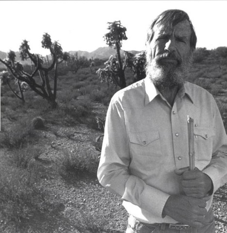 Books by Edward Abbey. Photograph with staff and desert landscape in background