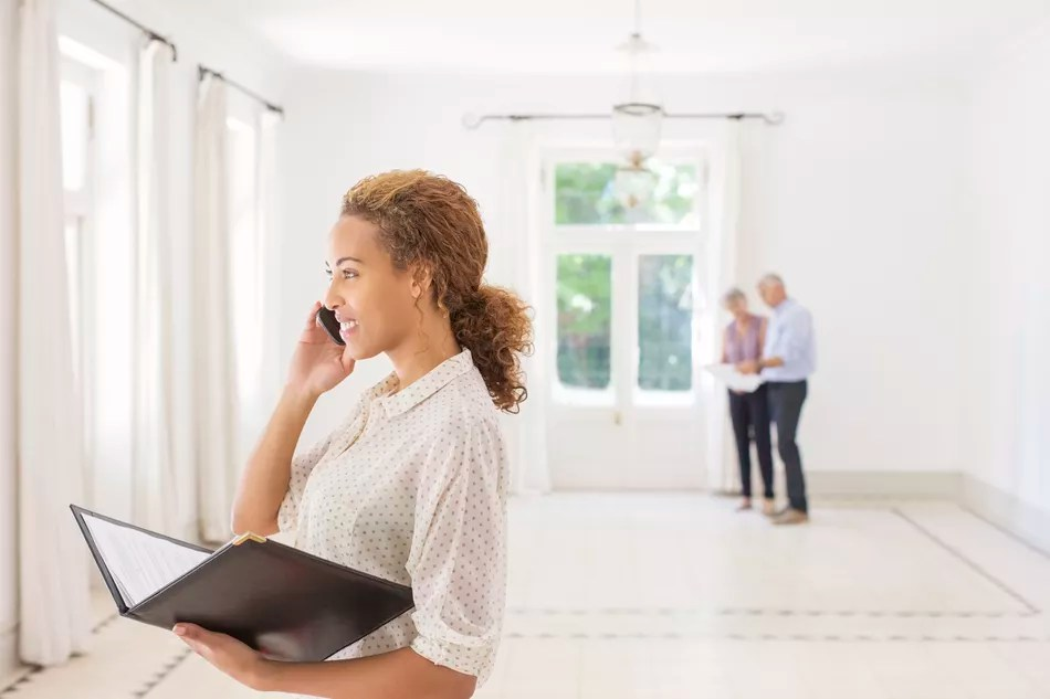A real estate agent talking on a phone while showing a house