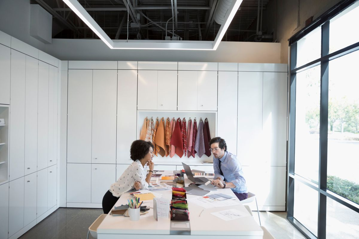 designers discussing fabric swatches in conference room meeting 719877233 5ac65fa4c0647100373358ec