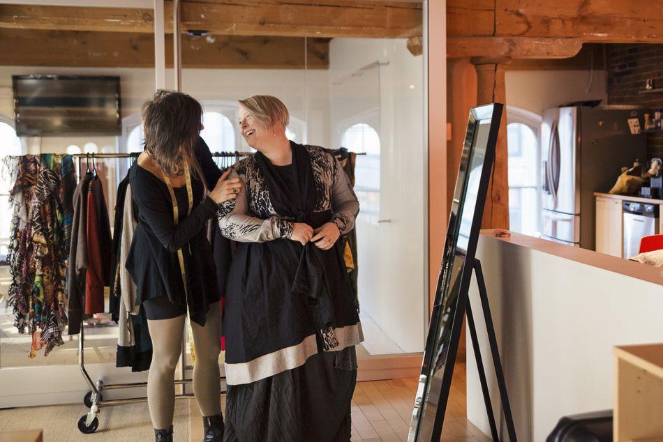 Fashion designer adjusting clothing on plus size woman.