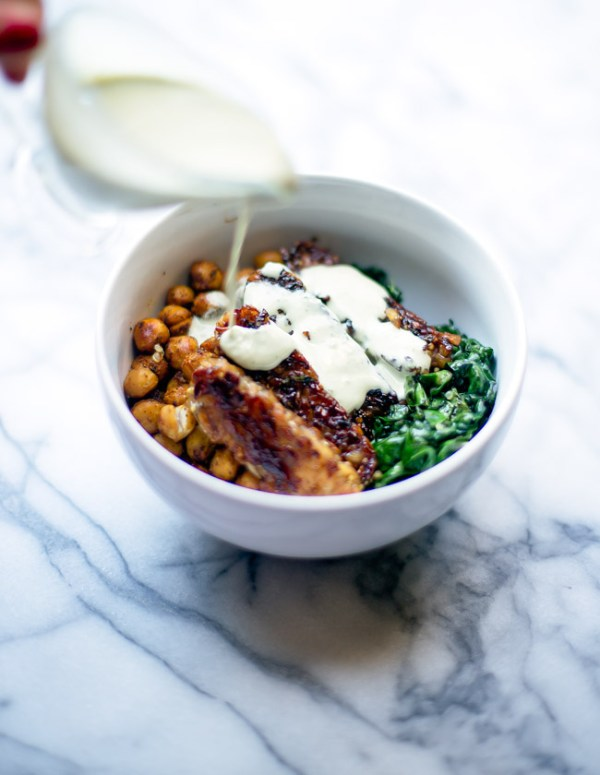 This hearty, satisfying bowl is packed with quinoa, kale, blackened tempeh, spiced chickpeas and is topped with a garlicky tahini sauce.