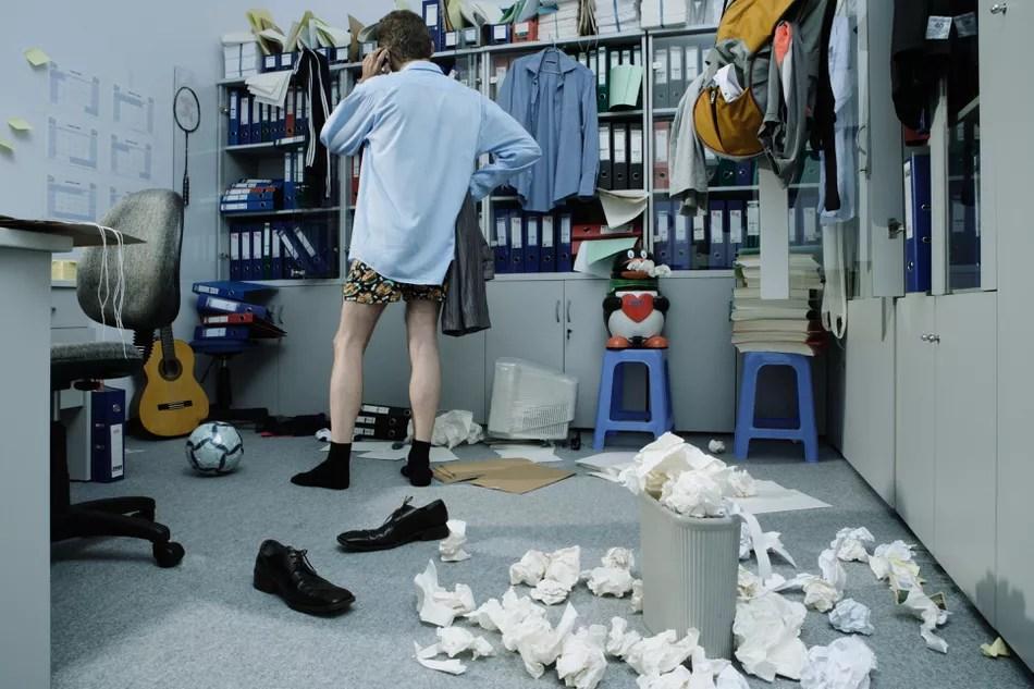 Homem sem calças no escritório bagunçado