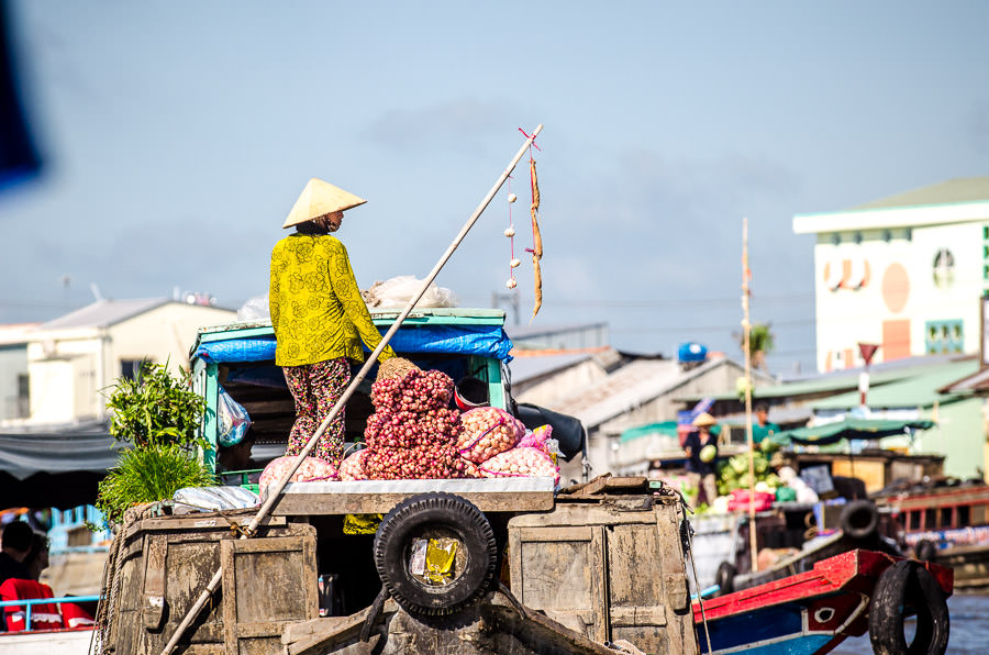 A Vietnamese woman working on her boat at the floating market.