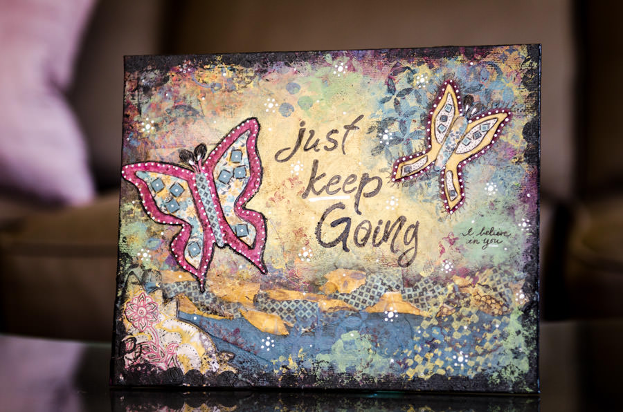 A canvas with butterflies that reads Just Keep Going