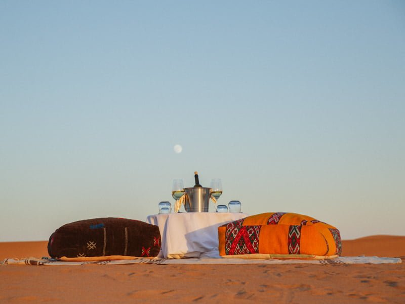 Chilled bottle of Wine in Ice Bucket and Pouf Seating in Moroccan desert