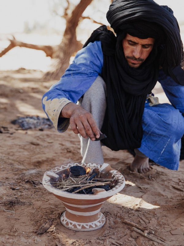 Berber Tribesman Lighting Barbeque Fire with Charcoal and Kindling in Earthenware Pot