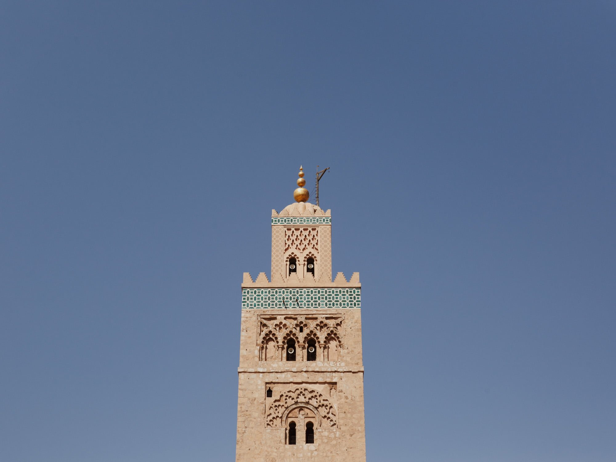 Top of the minaret tower at Koutoubia Mosque includes a dome, a spire with gilded copper balls (jamur) and a gibbet like flagpole