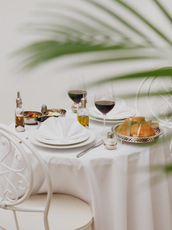 Main Moroccan Meal, Glasses of Wine, salads, tajines, rice dishes and napkins
