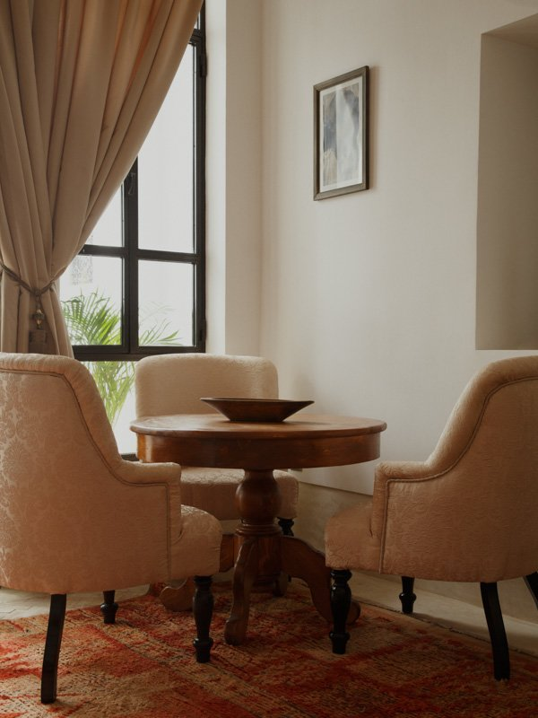 Moroccan Armchairs, small Dining Table with Fruit Bowl, Tied Back Curtains at Window
