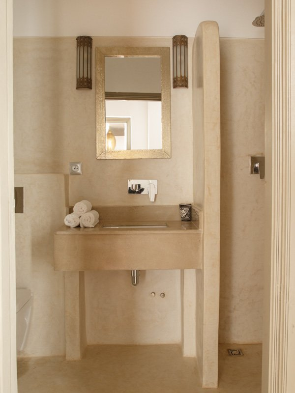 Luxury bathroom with cream marble basin, gold frame vanity mirror and cream marble tiles