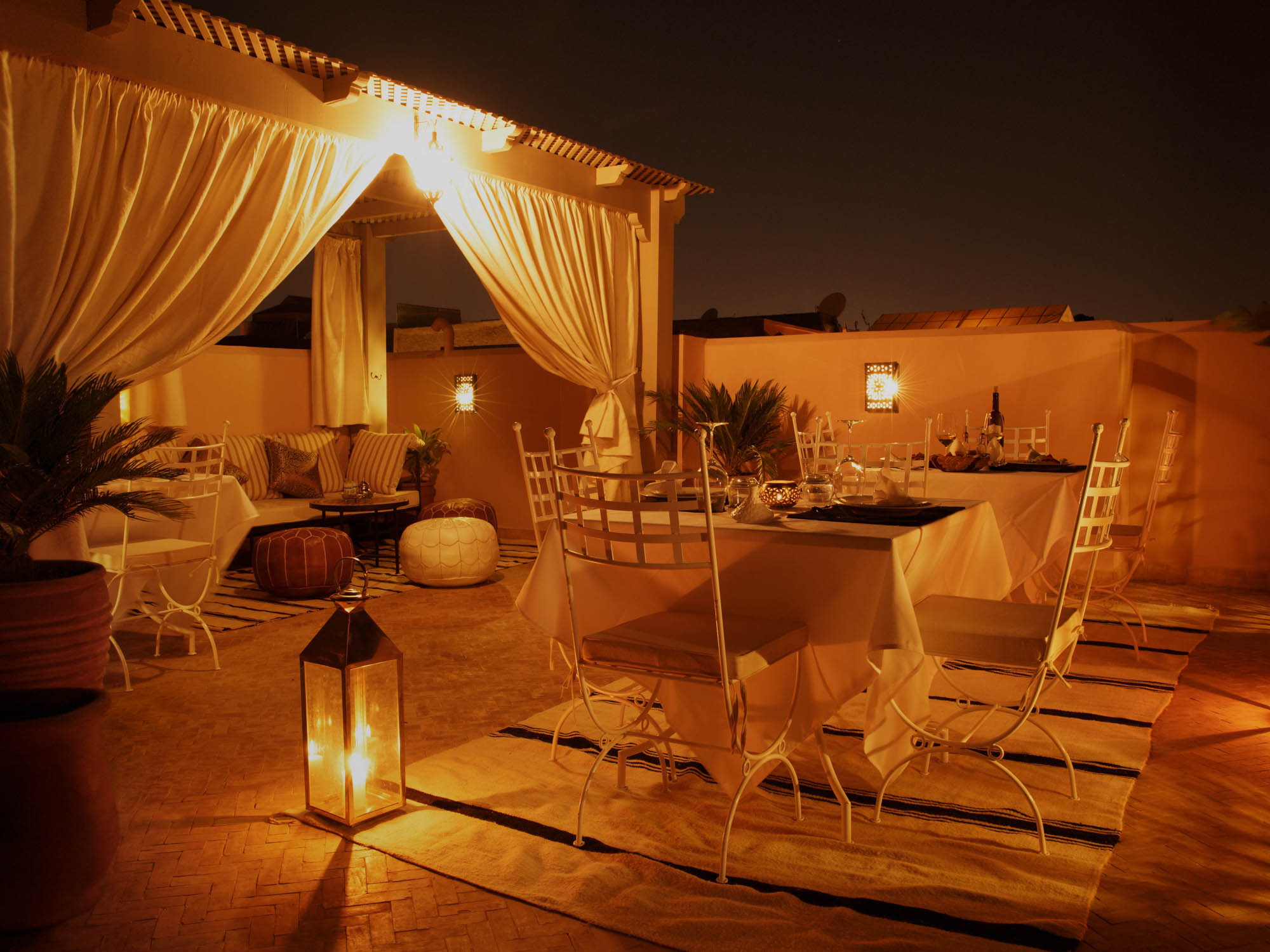 Al Fresco Dining, Moroccan Poufs and Cushions on Couch on Luxury Rooftop patio at Riad Boutique Hotel.