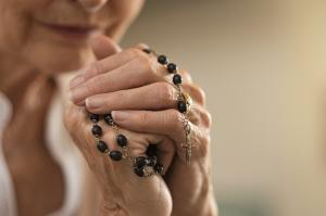Hands holding rosary and praying