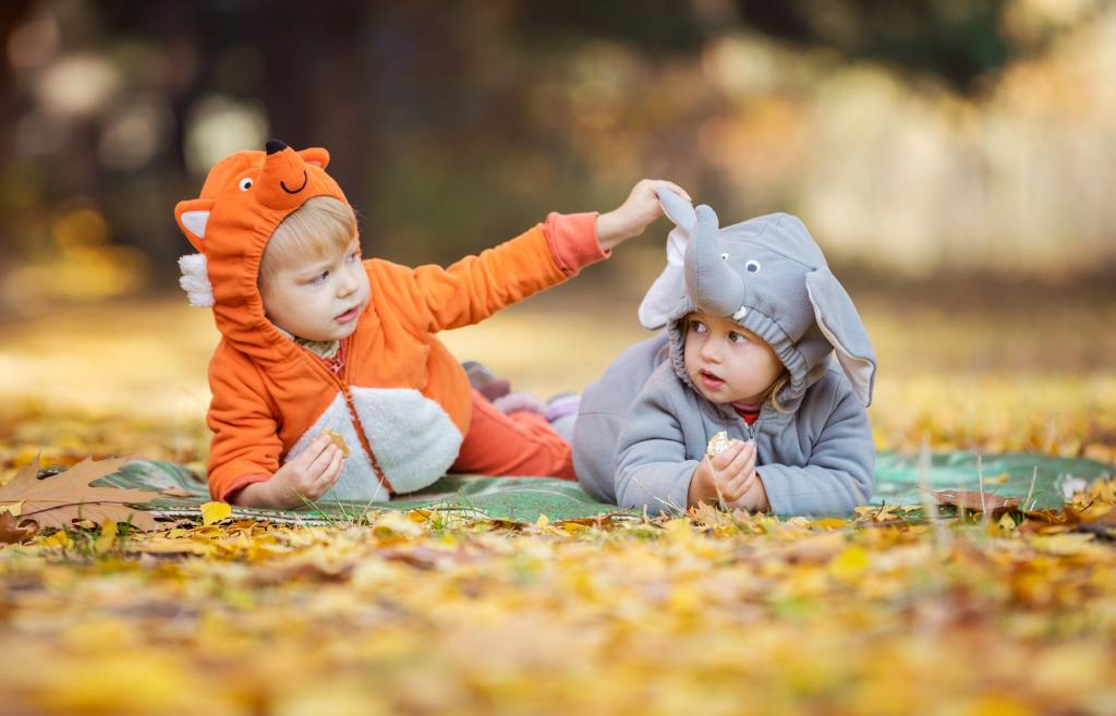 Little children in animal costumes playing in autumn forest