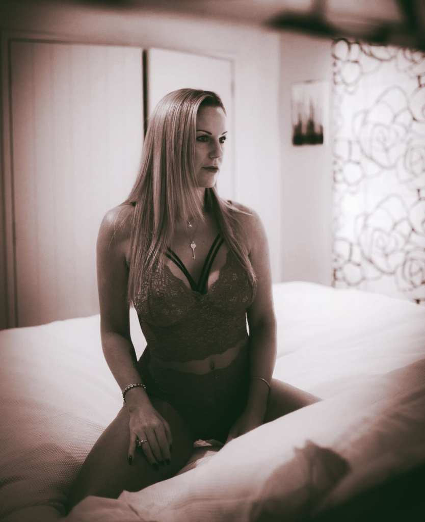 A black and white photograph of a woman wearing lingerie sitting on her bed looking at a mirror