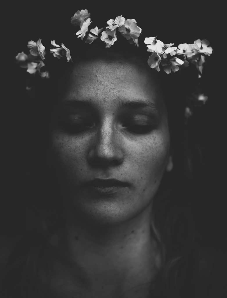 A close up black and white photograph of a woman with flowers on her head