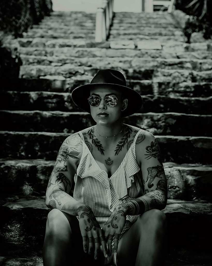 A black and white photograph of a woman with tattoos sitting on steps