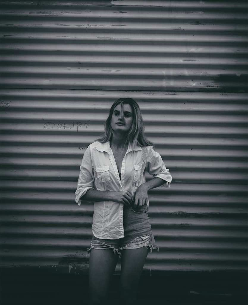 A black and white image of a woman with light hair standing in front of a garage door