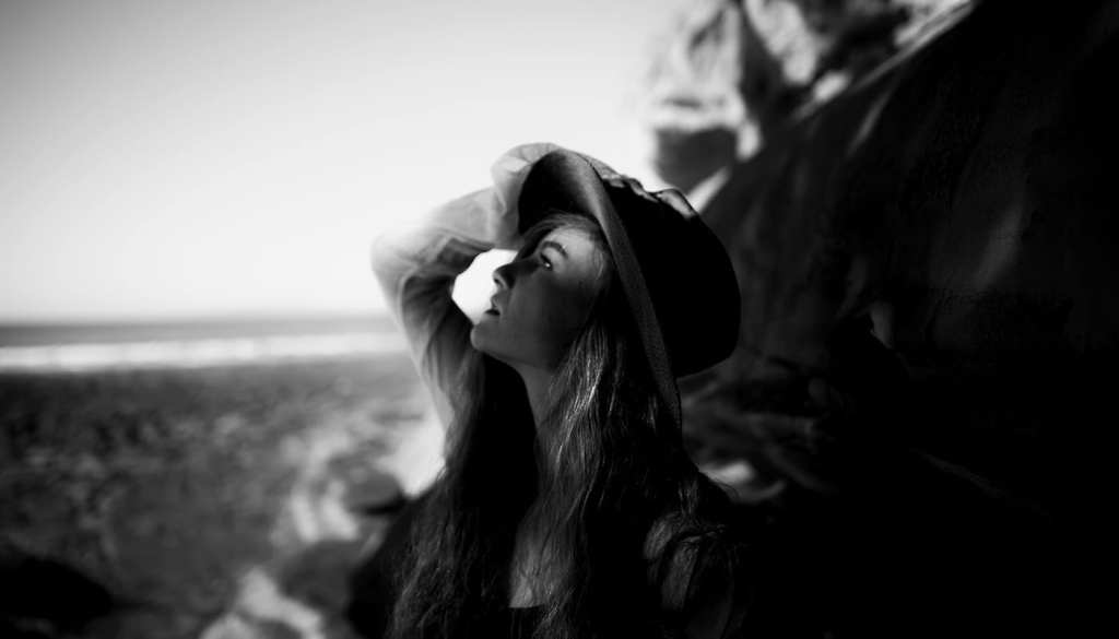 A black and white photo of a woman looking to the sky with a hat