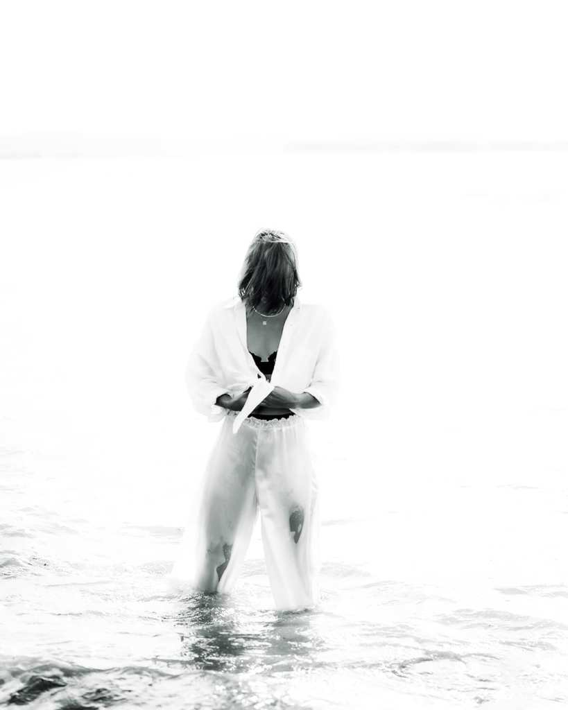 a woman in a white suit standing on the water's edge